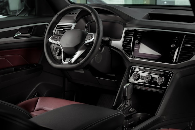 New automobile interior details with leather steering wheel, automatic transmission and touchscreen center console