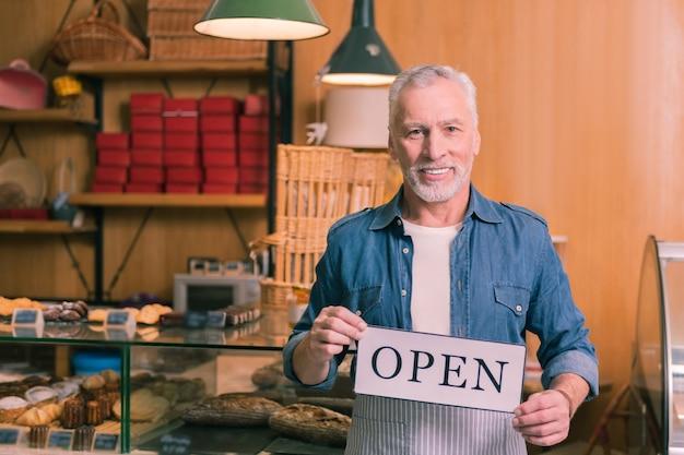 새로운 빵집. 그의 새로운 프랑스 빵집을 여는 쾌활한 느낌의 번영하는 사업가 수염