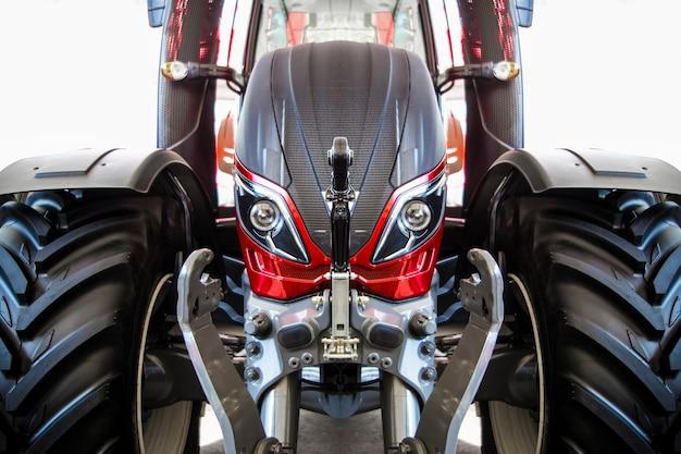 新しい、美しい、黒のホイールトラクター、クローズアップ、背景画像と赤