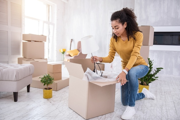New beginning. charming curly-haired girl packing a white lamp into the box while packing her belongings before moving out