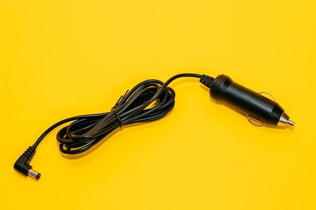 黄色の背景に新しい黒のシガレットライタープラグ