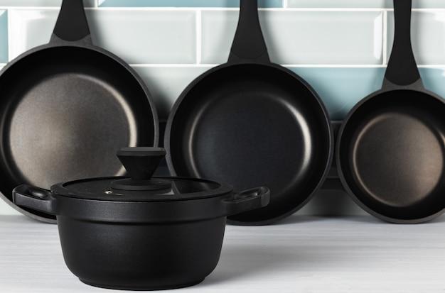 青いタイルの壁に新しい黒い調理器具