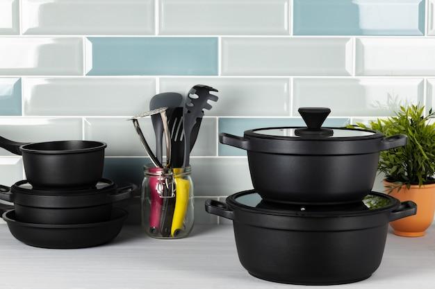 Новая черная посуда на синей плиточной стене
