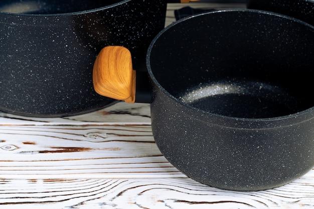 Новая черная посуда с деревянными ручками крупным планом