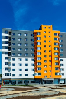 New block of modern apartments with balconies and blue sky in the background