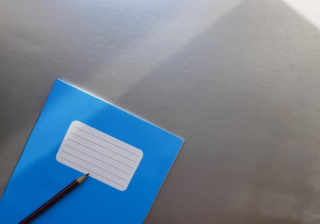 Новый синий блокнот с карандашом на сером столе с солнечными лучами от фона окна.