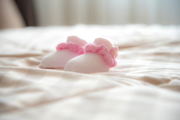 The new born baby's socks on the bed in warm tone