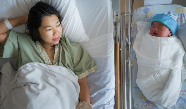 生まれたばかりの赤ちゃんは母親と一緒に病院で眠る