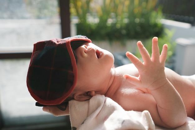 Новорожденный ребенок загорает под утренним солнцем дома у окна