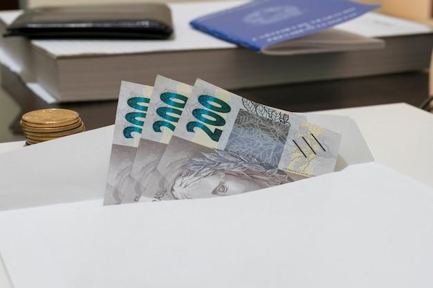 硬貨と書類が入ったテーブルの封筒に入った新しいブラジルの法案200レアル