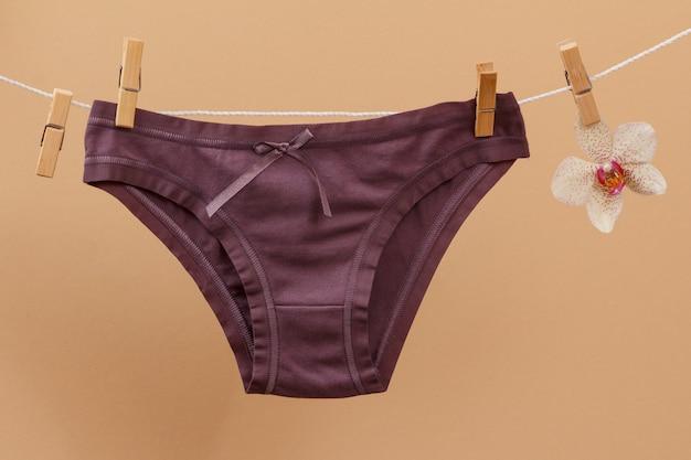 ベージュの背景に洗濯バサミと蘭の花が付いた物干し用ロープの新しい茶色の綿のパンティー。女性の下着。