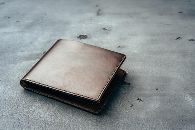Новый коричневый кожаный кошелек на темном фоне крупным планом