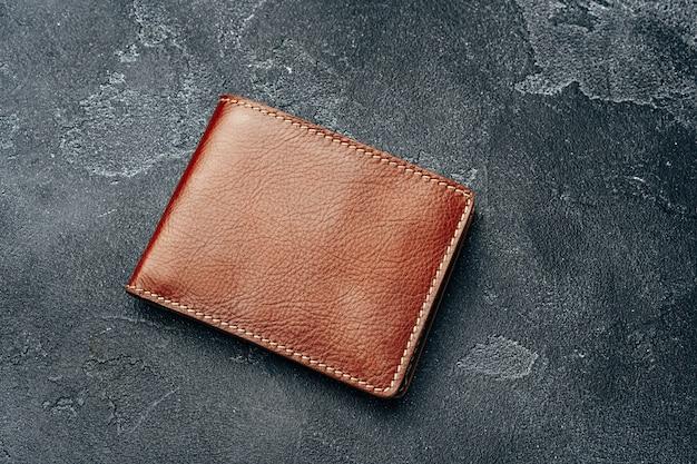 어두운 배경에 새로운 갈색 가죽 지갑을 닫습니다.
