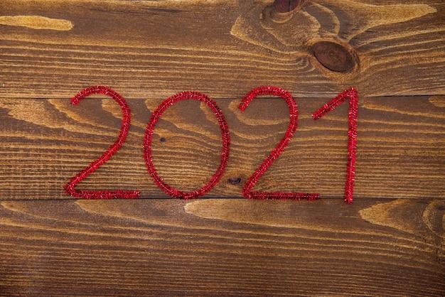 Новая коричневая деревянная поверхность из темного натурального дерева с красными новогодними числами 2021