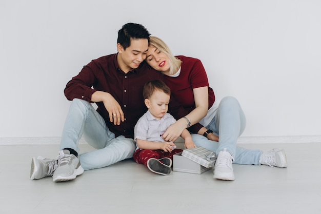 New building residential house purchase apartment concept. multicultural family with son sitting on the floor, caucasian mom and asian dad with their son