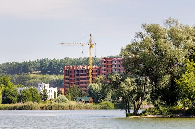 生態学的にクリーンなゾーンの川の近くにクレーンがある新しい建物