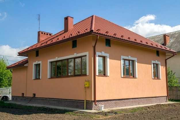 New built one-store cottage house with red tiling roof, plastic windows, plastered walls and high chimneys on fenced land plot in quiet neighborhood. construction and real estate property concept.