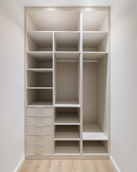 Новая встроенная мебель в небольшой гардеробной современной кладовой с гардеробом, множеством полок и ящиков.