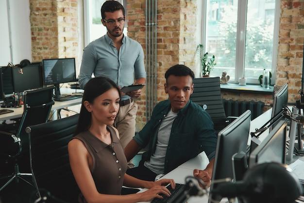 Группа молодых сотрудников новой бизнес-стратегии, глядя на монитор компьютера и что-то обсуждая
