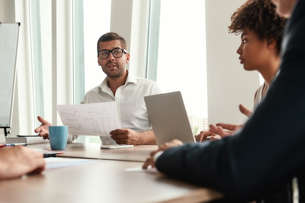 財務報告書を保持し、正装と眼鏡の新しいビジネス戦略の若者