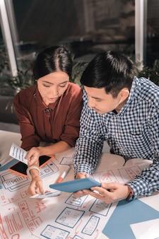 新しいビジネス。新しいビジネスについて考えることに関与していると感じているビジネスマンのカップルの上面図