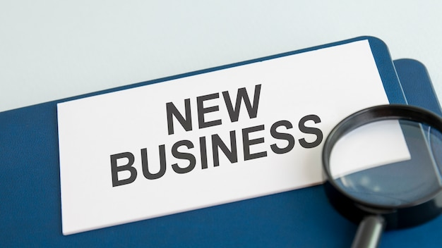 New business word on white paper card and magnifying lens