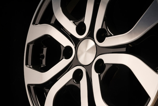 New car alloy wheel, close-up on a black wall, wheel elements, two-color coating, shiny.