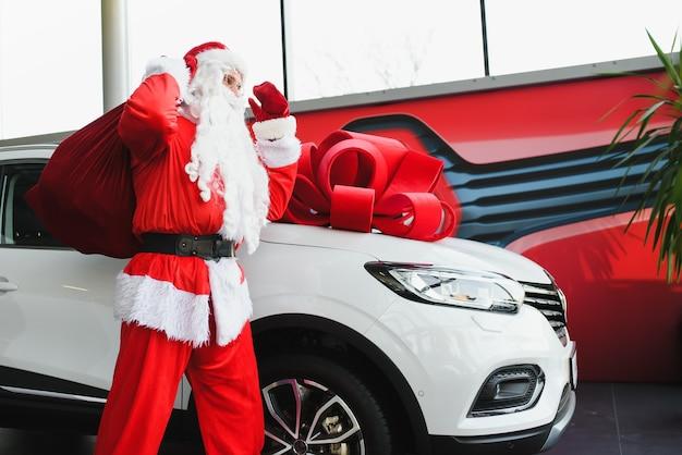 크리스마스 선물로 새 차. 새 차 근처 자동차 쇼룸에 산타 클로스.