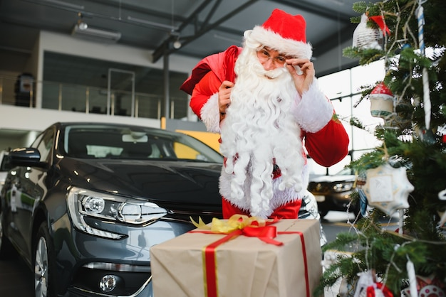 Новая машина в подарок на рождество. дед мороз в автосалоне возле новой машины.