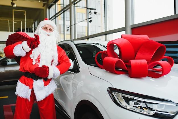 New car as a christmas present. santa claus in the car showroom near a new car.