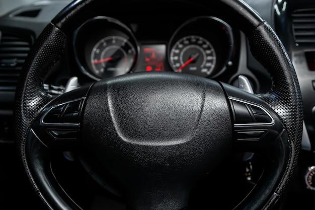 新しい車のインテリアの詳細。スピードメーター、タコメーター、ステアリングホイール
