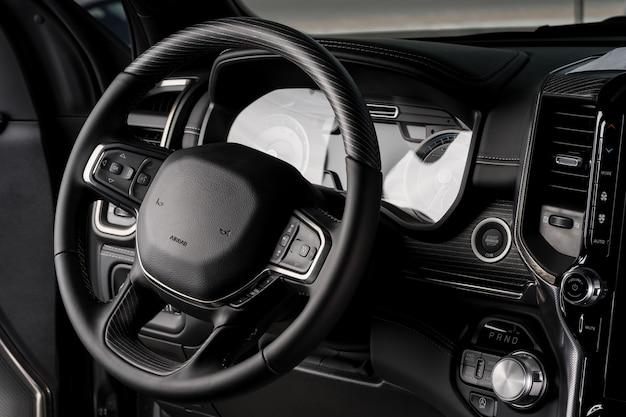 Новый автомобиль в салоне рулевого колеса, электрическая панель приборов крупным планом - подушка безопасности