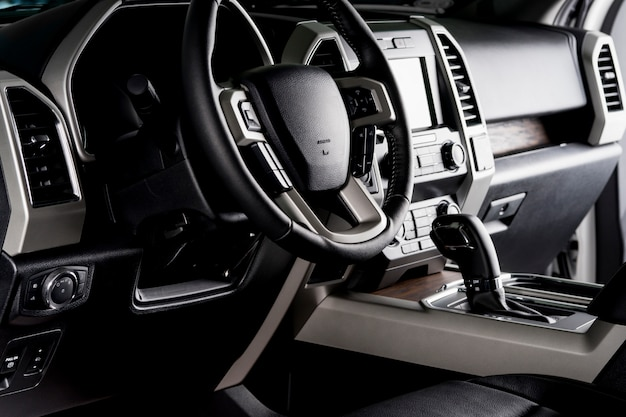 New car interior with luxury details, automatic transmission and steering wheel with electric buttons - dark lighting
