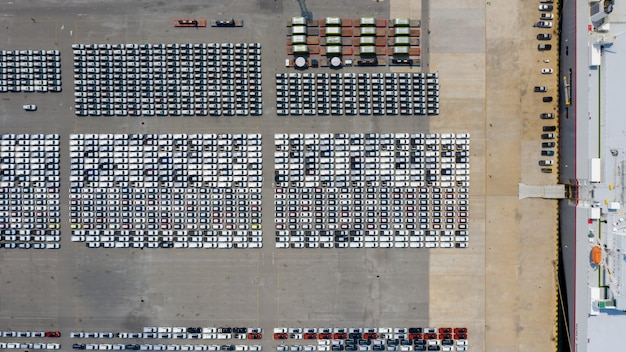New car line up parking lot automobile factory  export international dealers by shipping transportation open sea aerial view