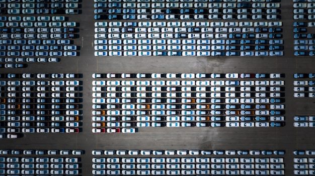 New car lined up in the port for business car import and export logistic, aerial view.