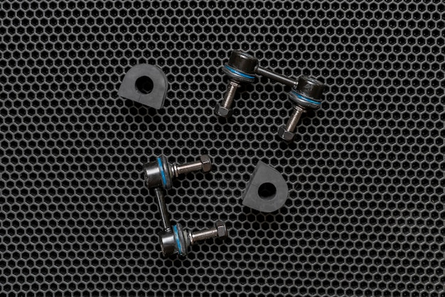 A new car spare parts, suspension details arms isolated on dark background flat lay