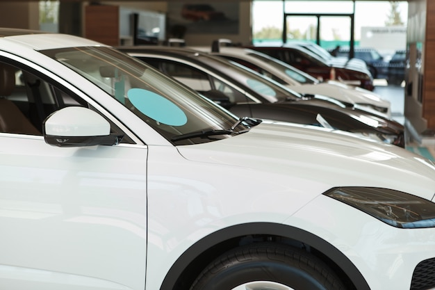 New cars parked in a row at dealership salon