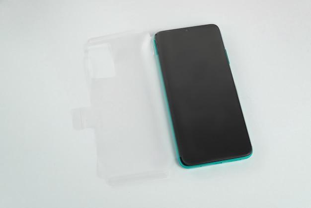 격리된 흰색 배경 위에 투명 덮개가 있는 새 휴대폰