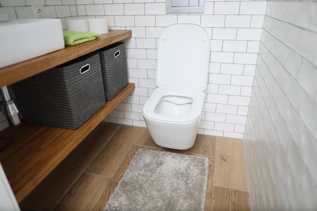 Новый керамический белый туалет на фоне светлой стены