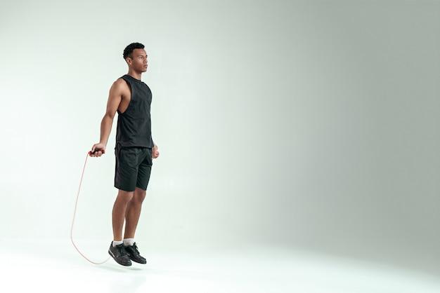 新しいチャンピオン。灰色の背景にスタジオで運動しながら縄跳びのスポーツ服を着た若いアフリカ人の全長。スポーツ用品。アクティブなライフスタイル