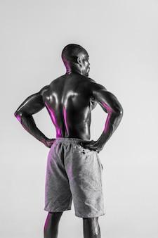 新しいチャンスが来ています。灰色の背景で若いアフリカ系アメリカ人のボディービルダーのトレーニングのスタジオショット。スポーツウェアに立っている筋肉の単一の男性モデル。スポーツ、ボディービル、健康的なライフスタイルの概念。