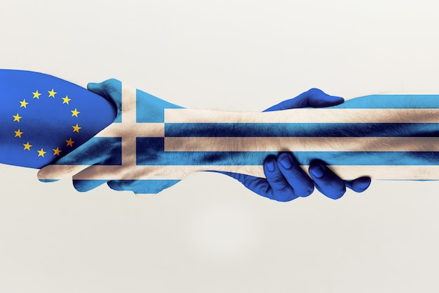 新しいチャンス。灰色のスタジオの背景に分離された青いeuとギリシャの旗で色を保持している男性の手。援助、連邦、国のパートナーシップ、政治的および経済的関係の概念。