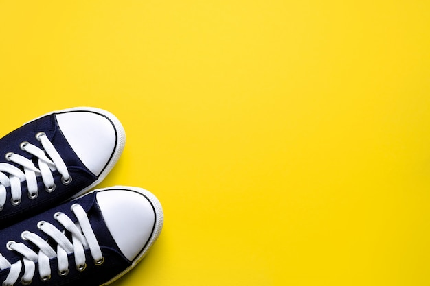 New clean blue sports sneakers with white laces, on a bright yellow background.