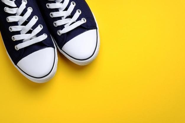 Новые чистые синие спортивные кроссовки с белыми шнурками, на ярко-желтом фоне.