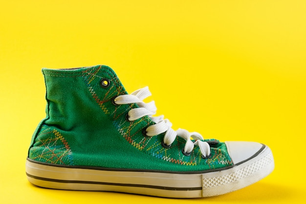New clean green athletic sneakers with laces on a bright yellow background.