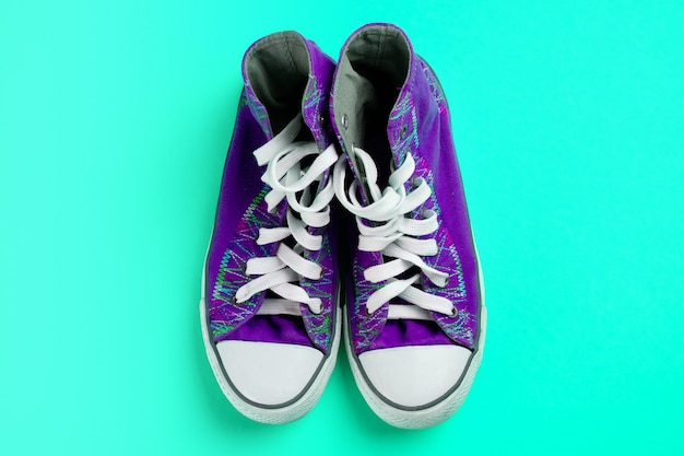 New clean purple athletic sneakers with laces on a bright pastel green background.