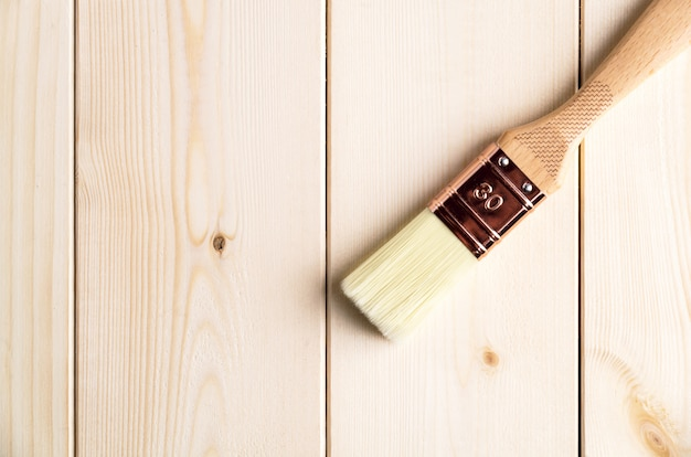 New clear paint brush on wooden surface