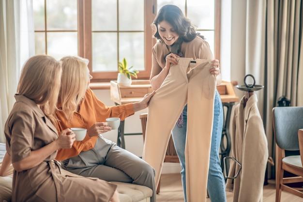 새 옷. 그녀의 친구에게 그녀의 새로운 구매를 보여주는 검은 머리 여자
