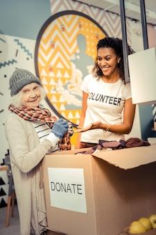 Новая одежда. радостная пожилая женщина, стоящая возле ящика для пожертвований, выбирая одежду для себя