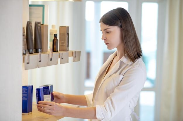 새로운 수집품. 가게에서 새로운 화장품을 면밀히 조사하는 검은 머리의 젊은 가게 조수